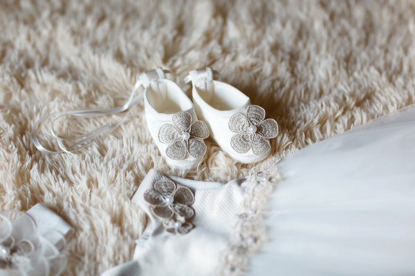 Close-up of white slippers and flower dresses for a newborn girl, concept of motherhood