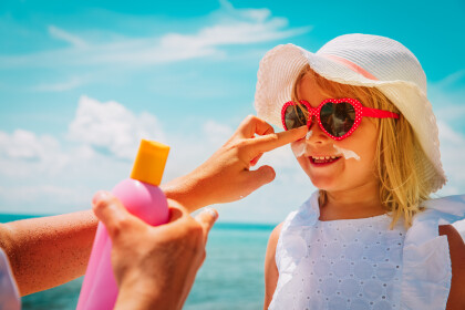 sun protection - mother put sunblock cream on little daughter face